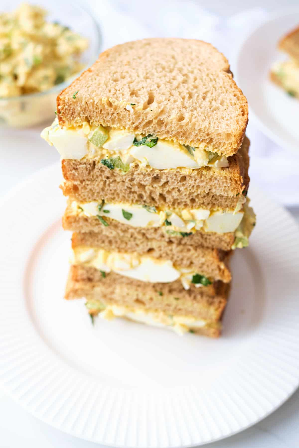 three-quarters view of a stack of completed Mexican Egg Salad Sandwiches