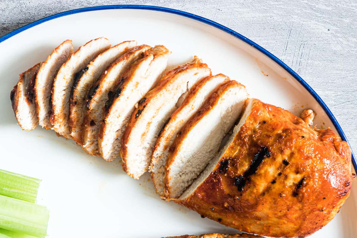 close up of a sliced grilled buffalo chicken breast on a plate