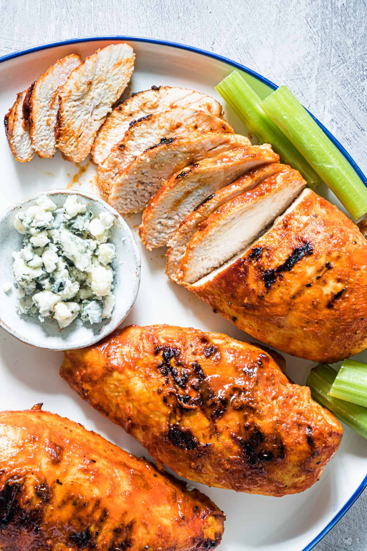 close up of grilled buffalo chicken on a plate with celery and cheese crumbles