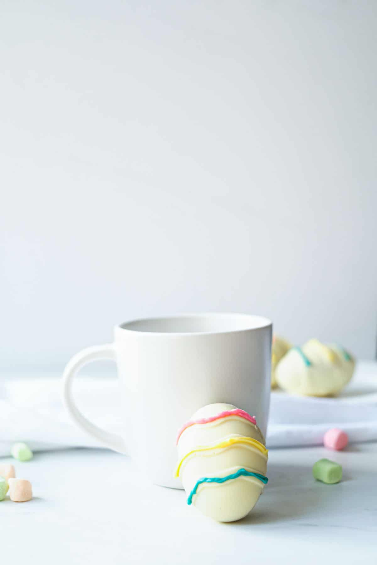 one Easter hot chocolate bomb leaning against a white mug