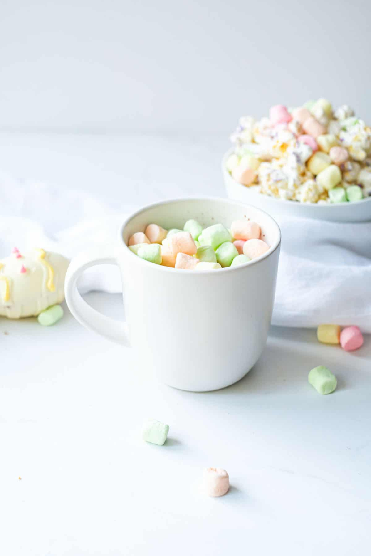 one white mug next to a completed Easter hot chocolate bomb and bowl filled with colored marshmallows