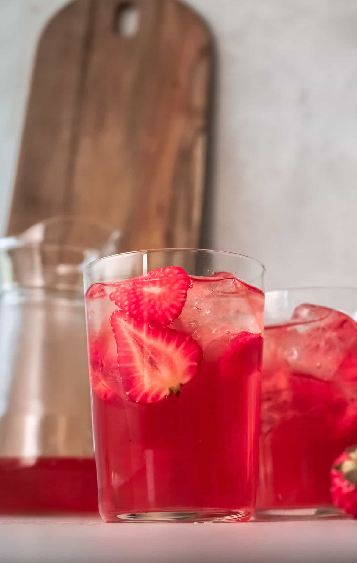 side view of two glasses filled with strawberry sweet tea