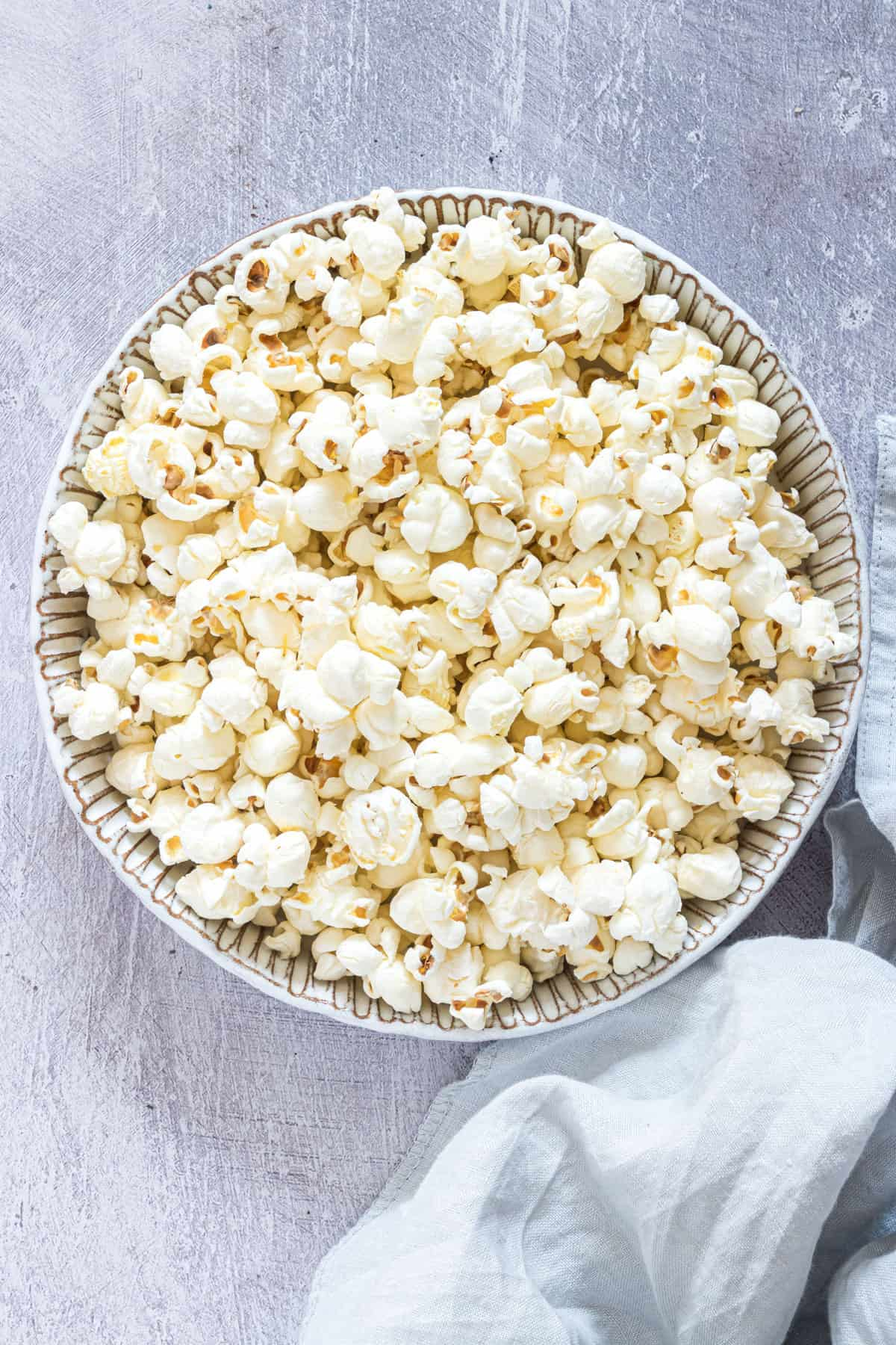 A bowl of air fryer popcorn on a table with a napkin