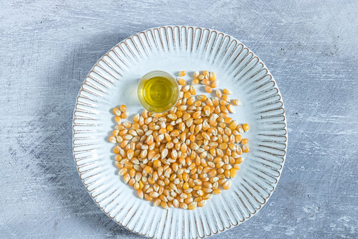 un-popped corn kernels and some oil on a plate