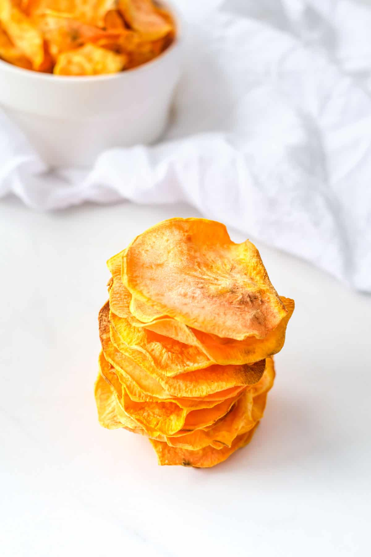 the completed air fryer sweet potato chips served in a white ceramic bowl