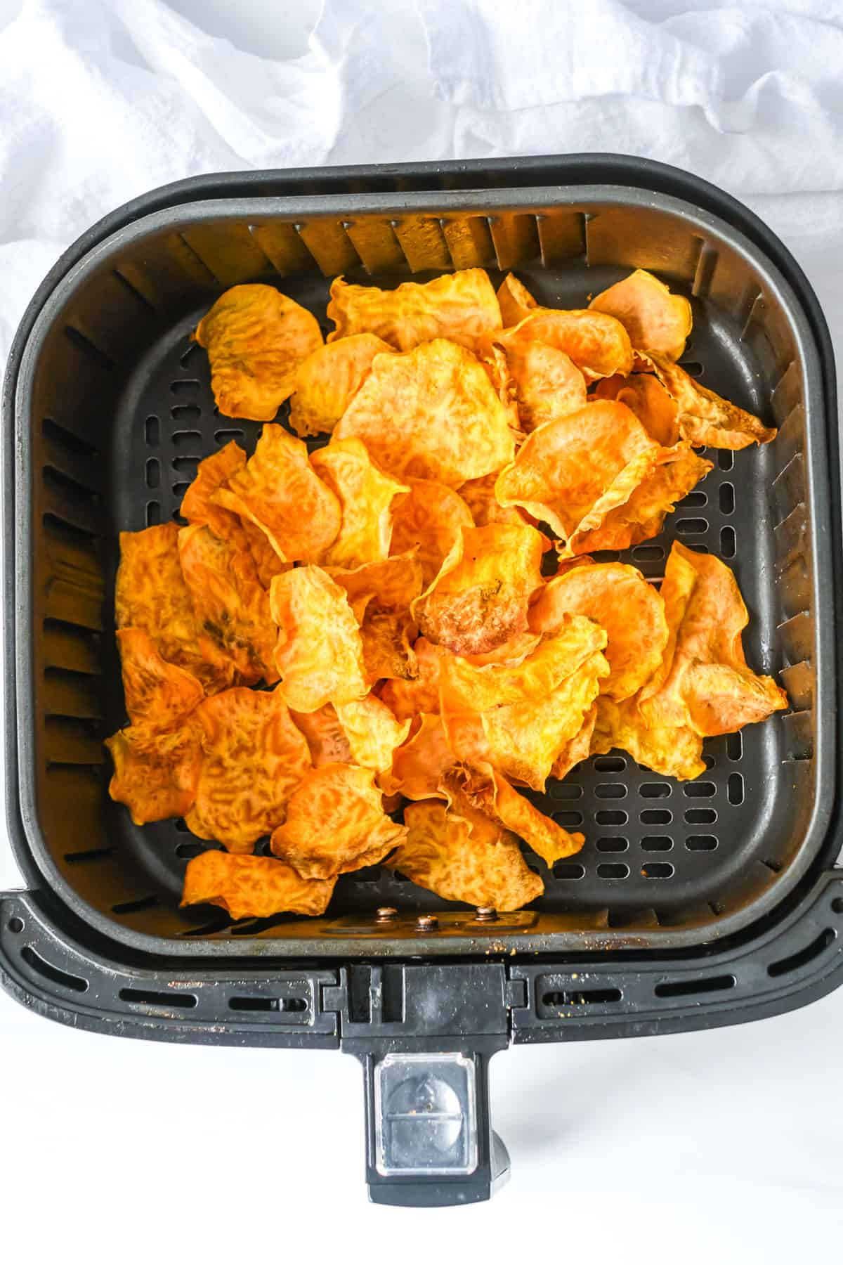 top down view of the cooked sweet potato chips inside the air fryer basket