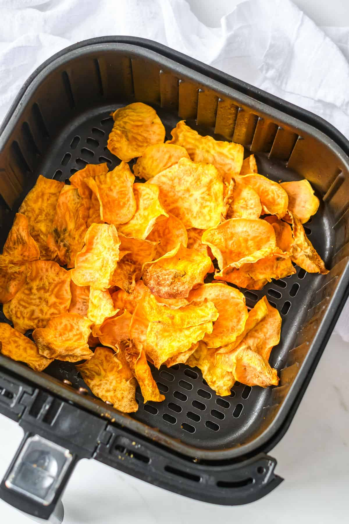 the finished air fryer sweet potato chips inside the air fryer basket