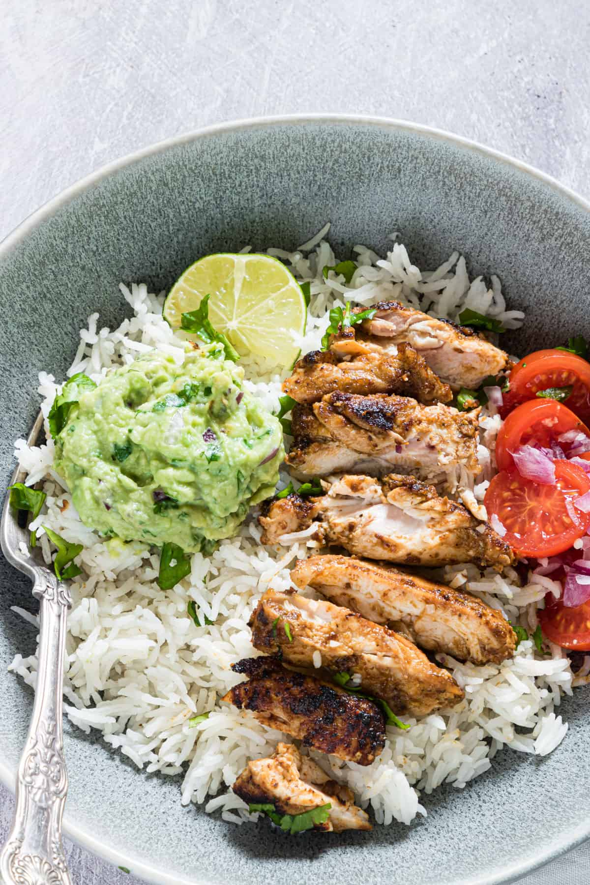 A meal prep bowl of chipotle chicken with rice and guacamole and salsa