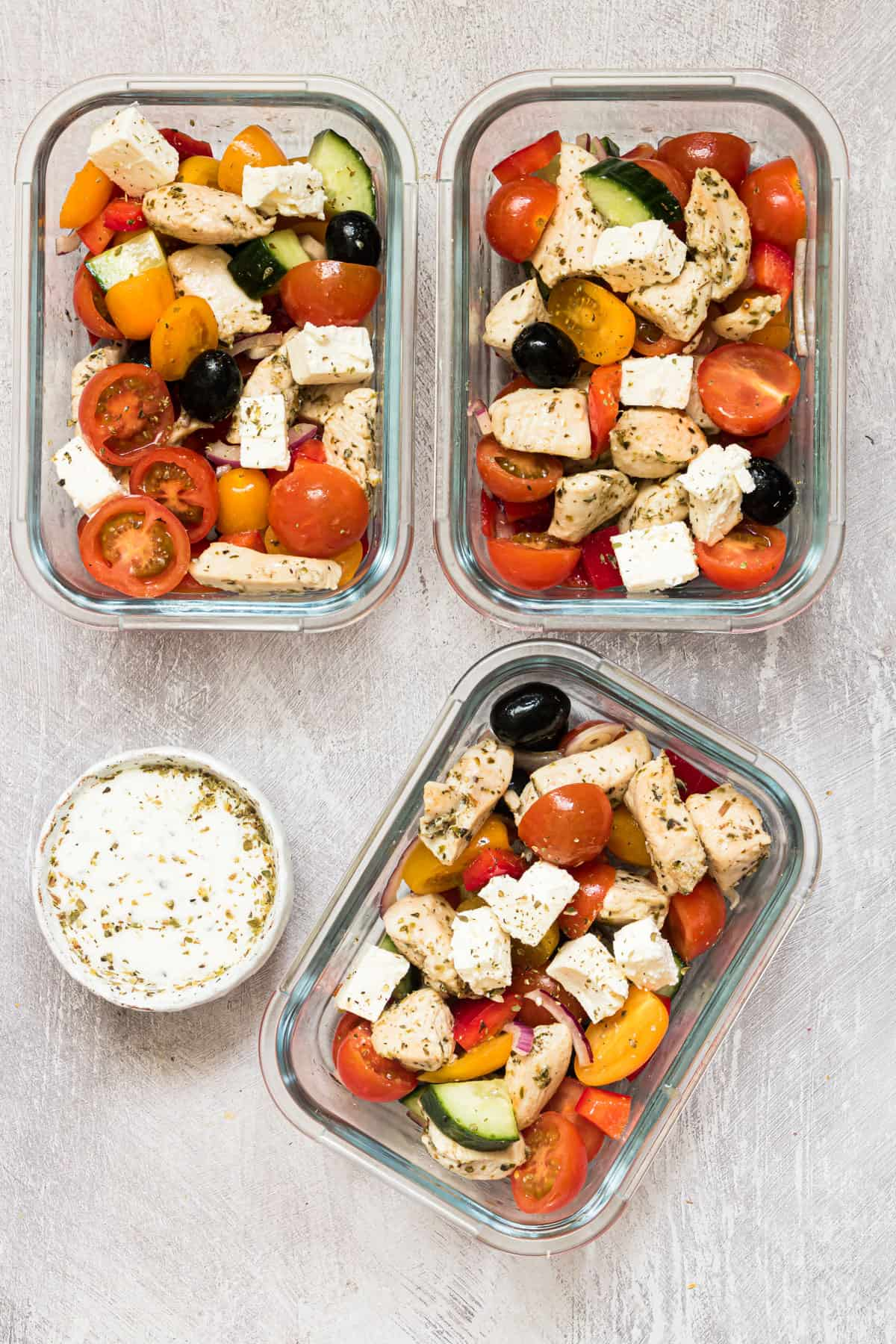 the finished greek chicken recipe in 3 meal prep containers with a dish of tzatziki sauce