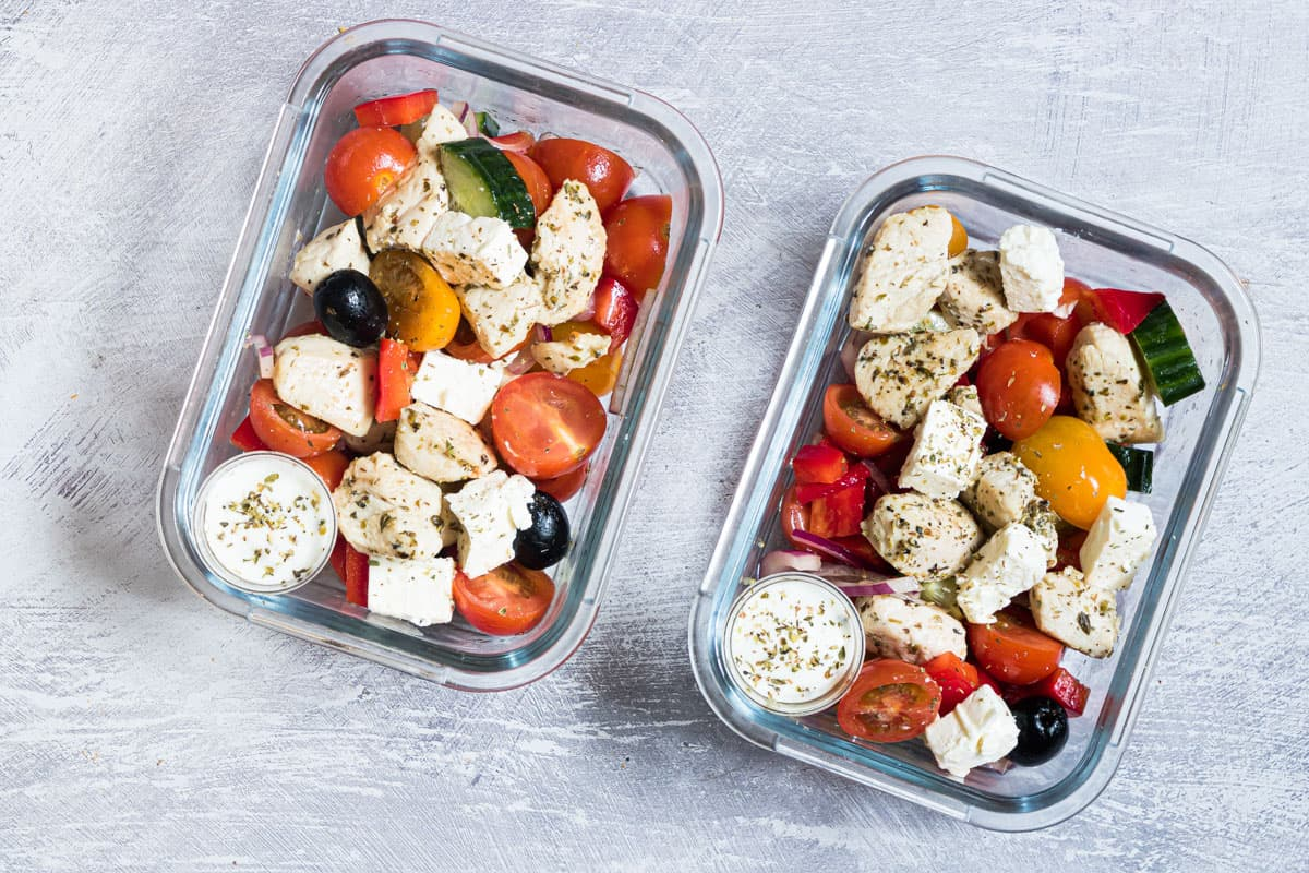 two meal prep containers filled with greek chicken and cucumber salad