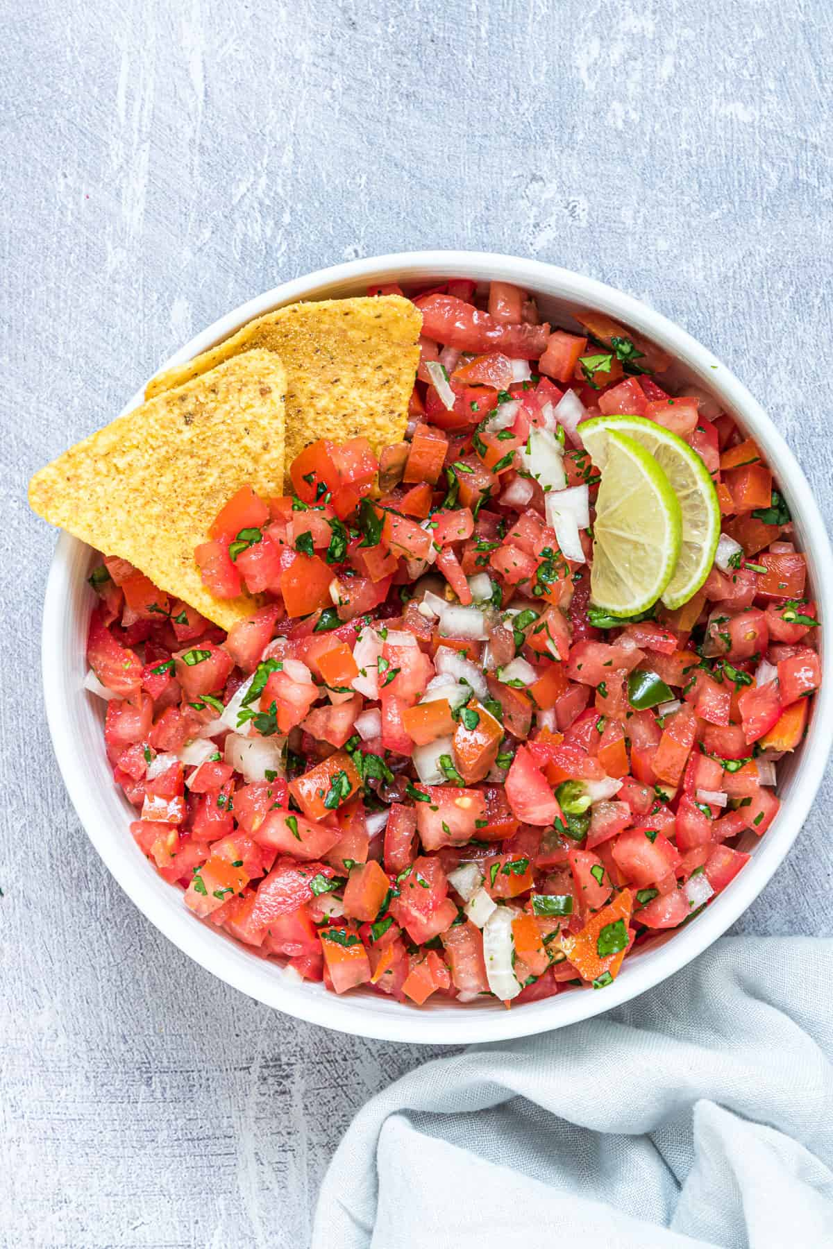 the finished pico de gallo in a serving bowl garnished with two chips and lime wedges