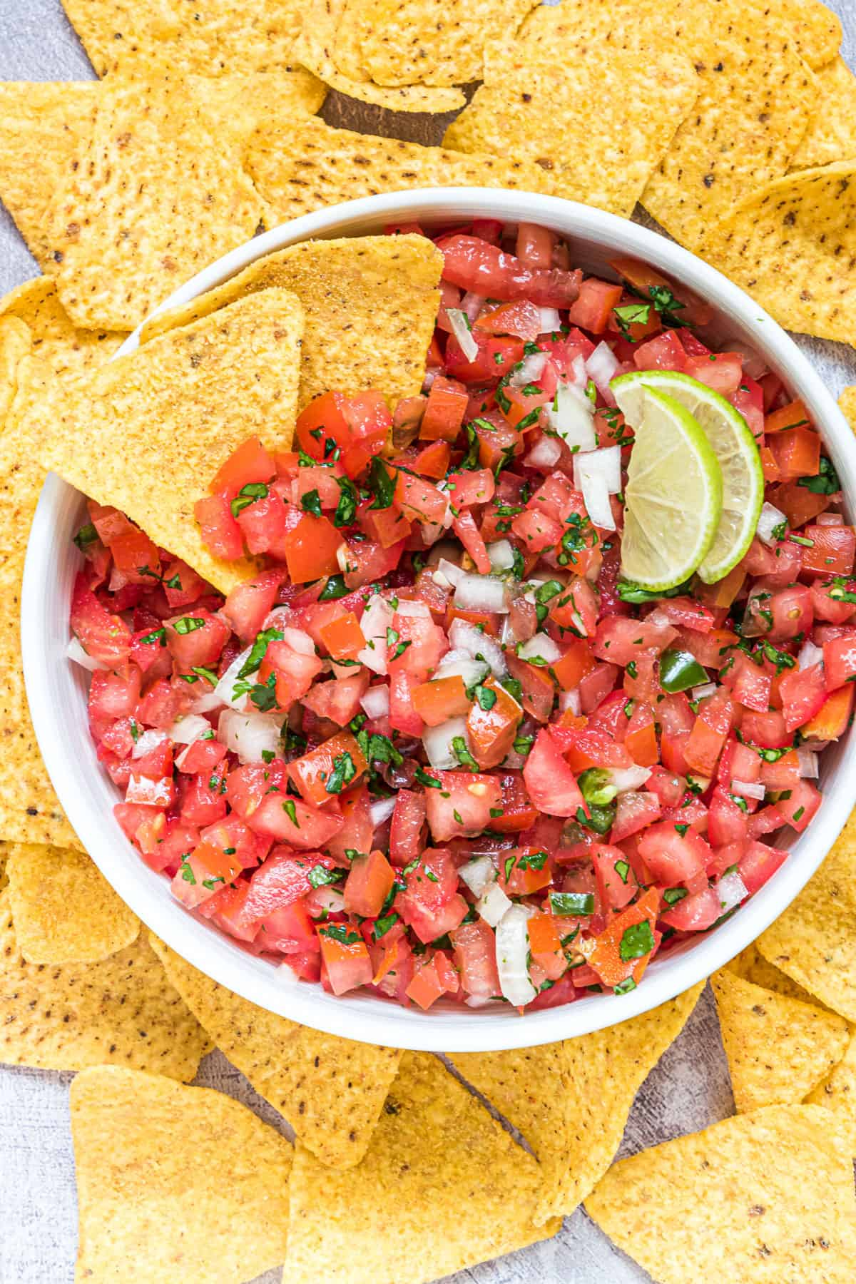 the completed Chipotle salsa recipe served in a white bowl with lime wedges and tortilla chips