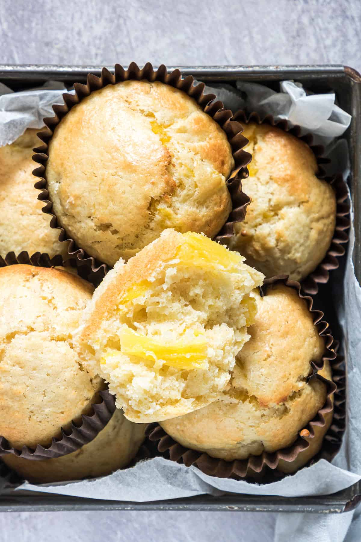 close up of some pineapple coconut muffins in a container.