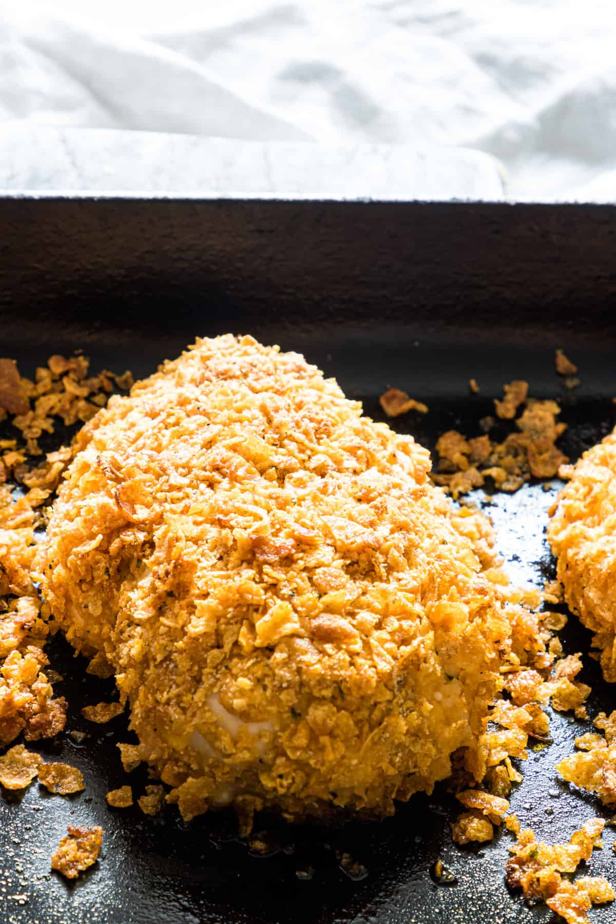 close up of baked chicken breast with cornflake crumbs around it