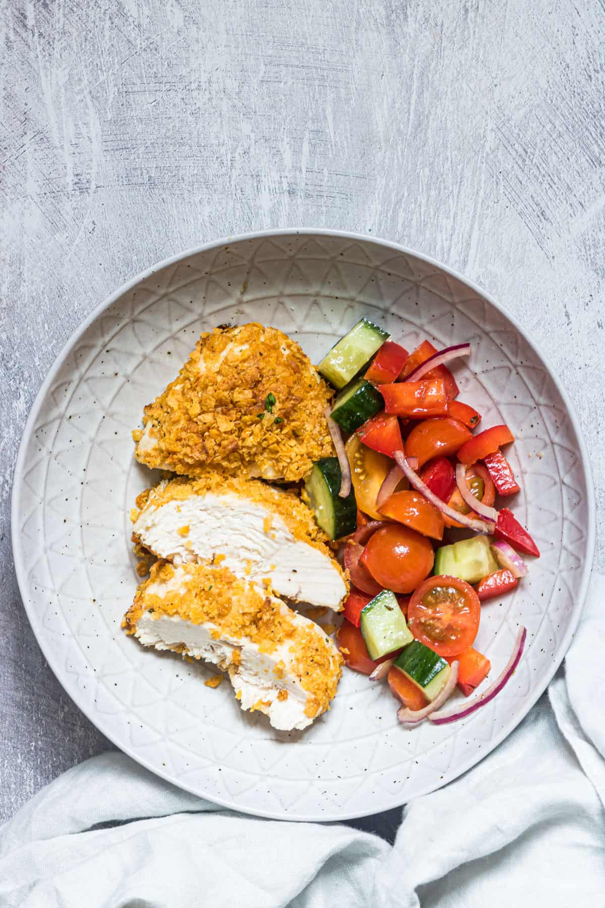 sliced baked chicken breast in a bowl with some salad