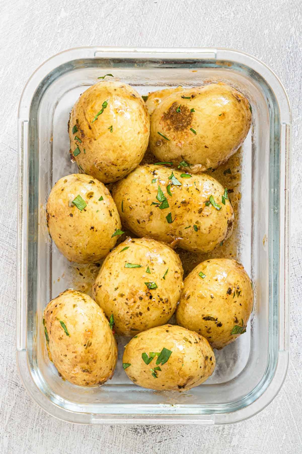 Instant pot baby potatoes in a meal prep glass jar with herbs sprinkled on top