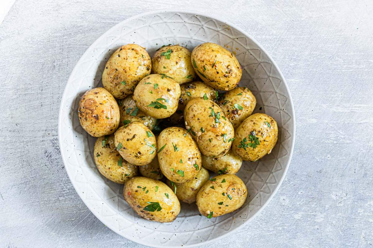 Instant pot small potatoes in a bowl with chopped herbs sprinkled on top