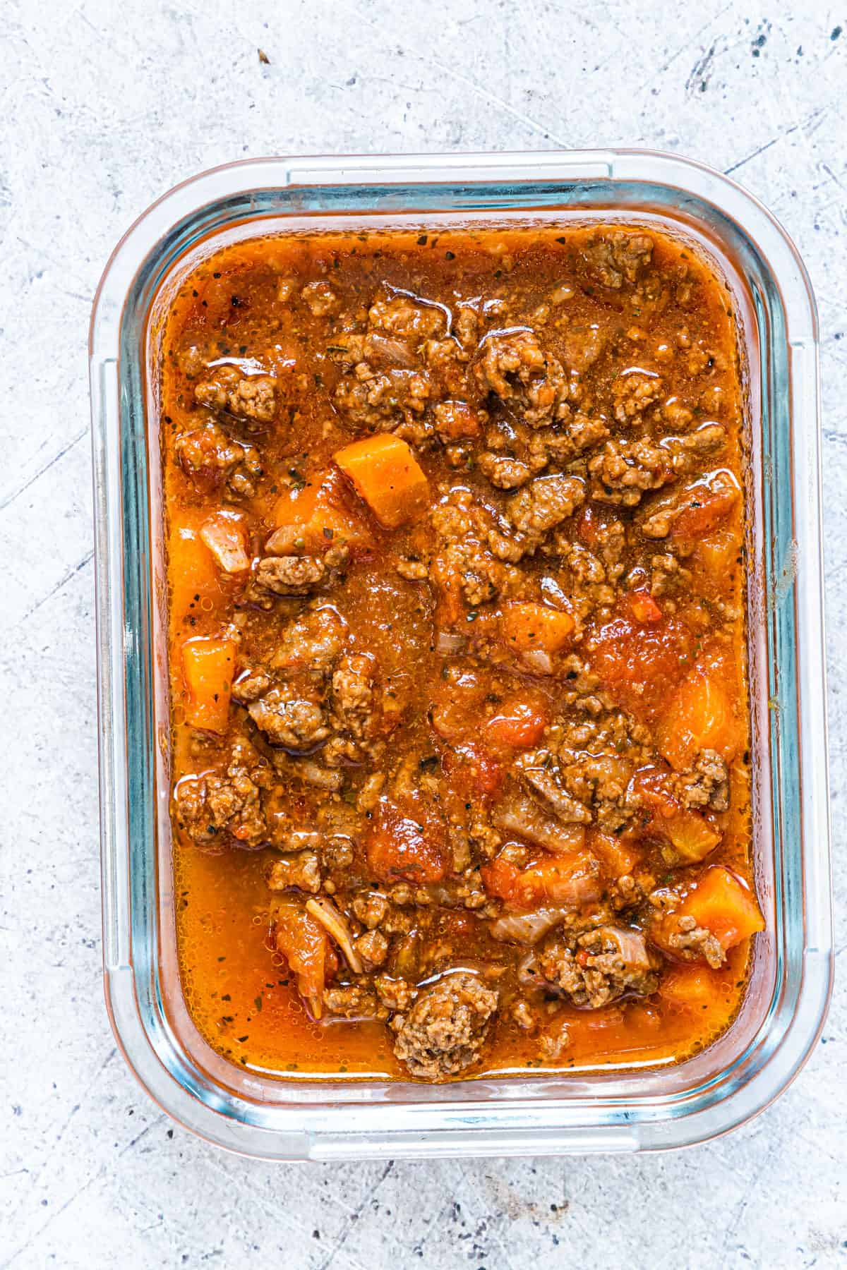 a portion of instant pot bolognese sauce in a glass storage container