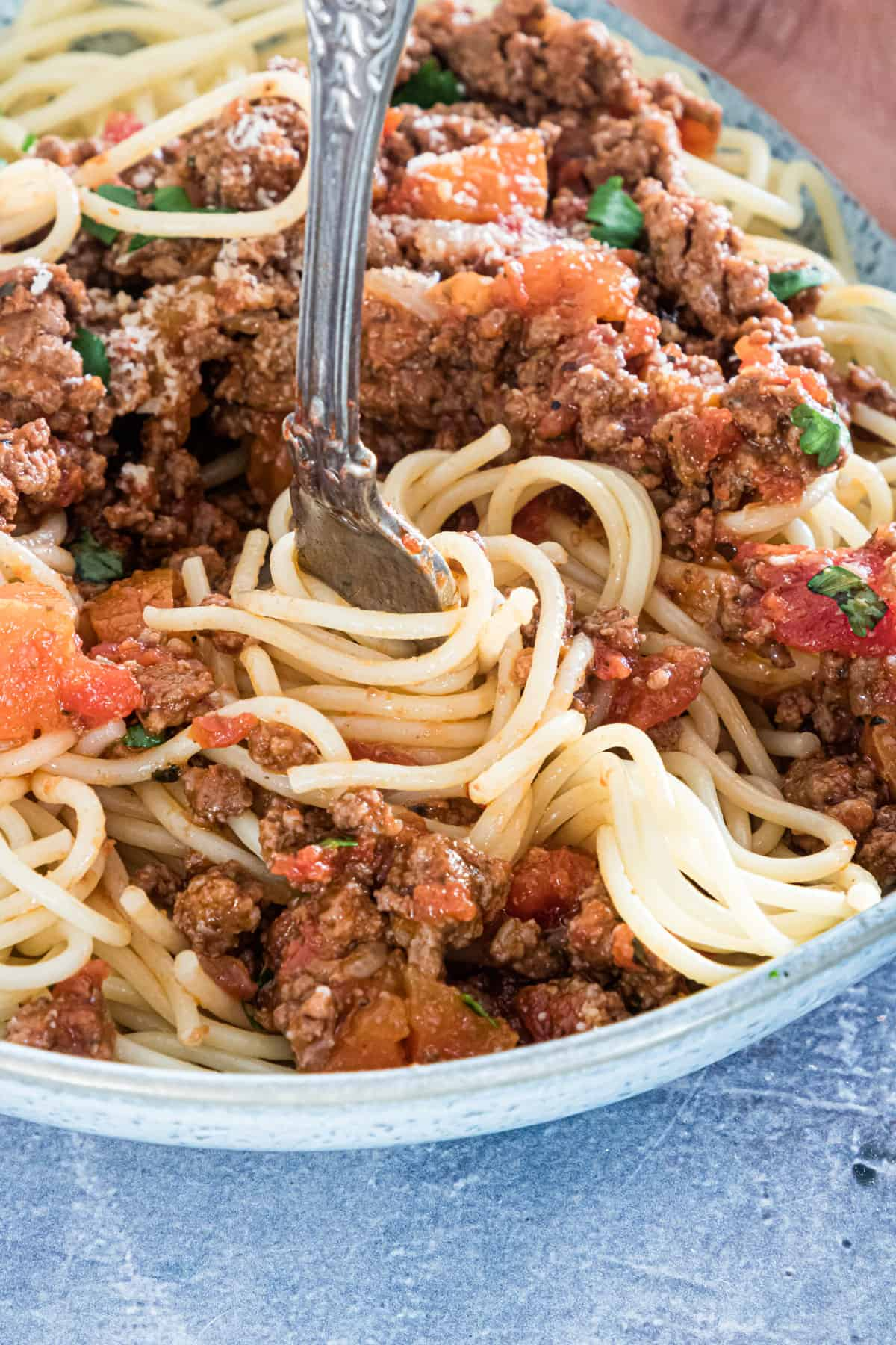 close up view of a fork removing a portion of bolognese sauce and pasta from a dish