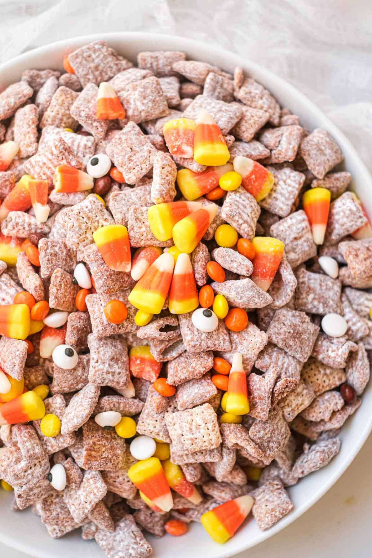 A bowl of halloween puppy chow with halloween candy and candy corn
