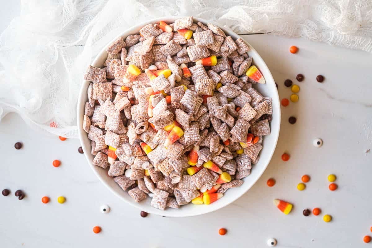 horizontal image of halloween puppy chow - halloween muddy buddies on a table with halloween candy sprinkled around