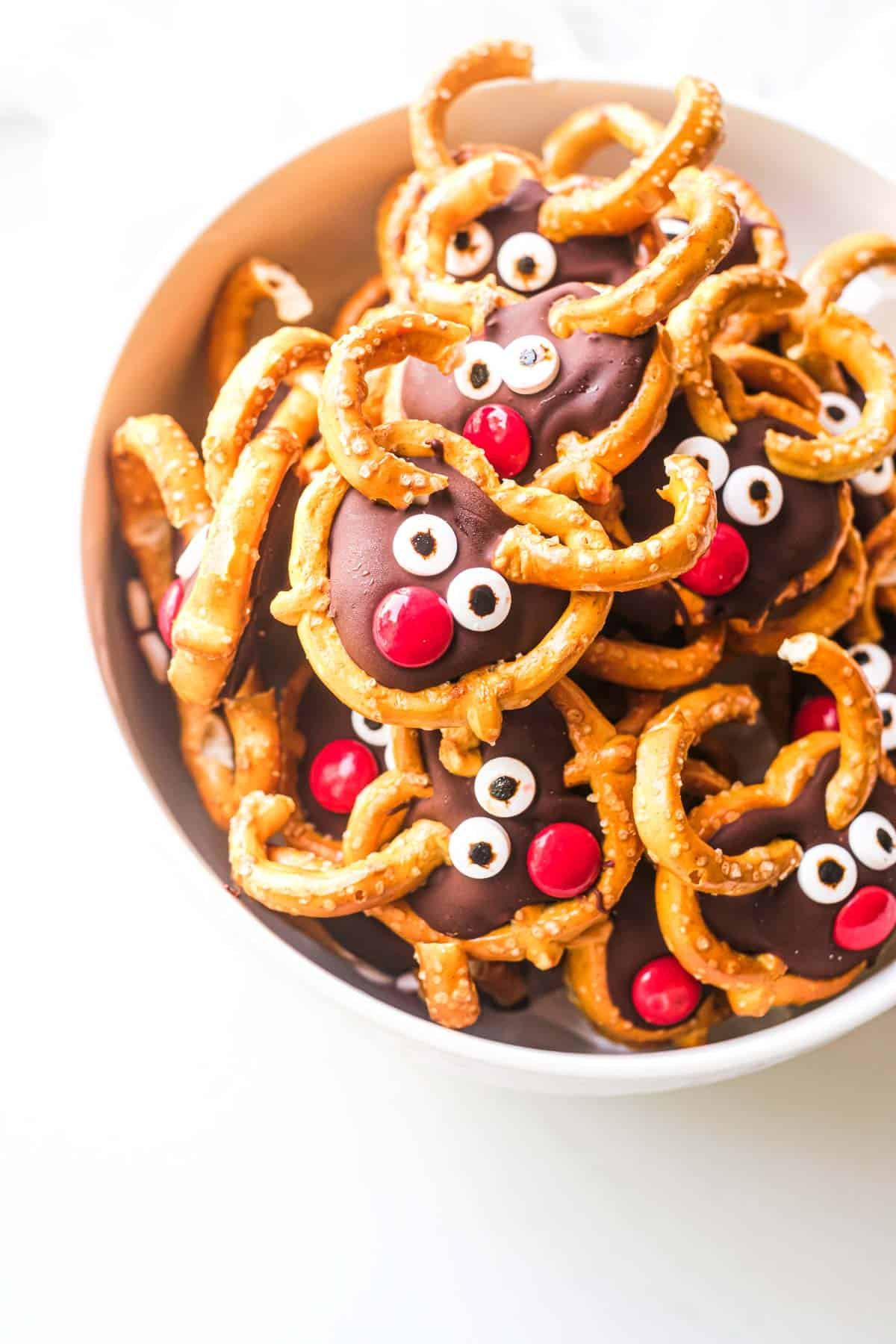 a bowl of colorful reindeer pretzels on a table