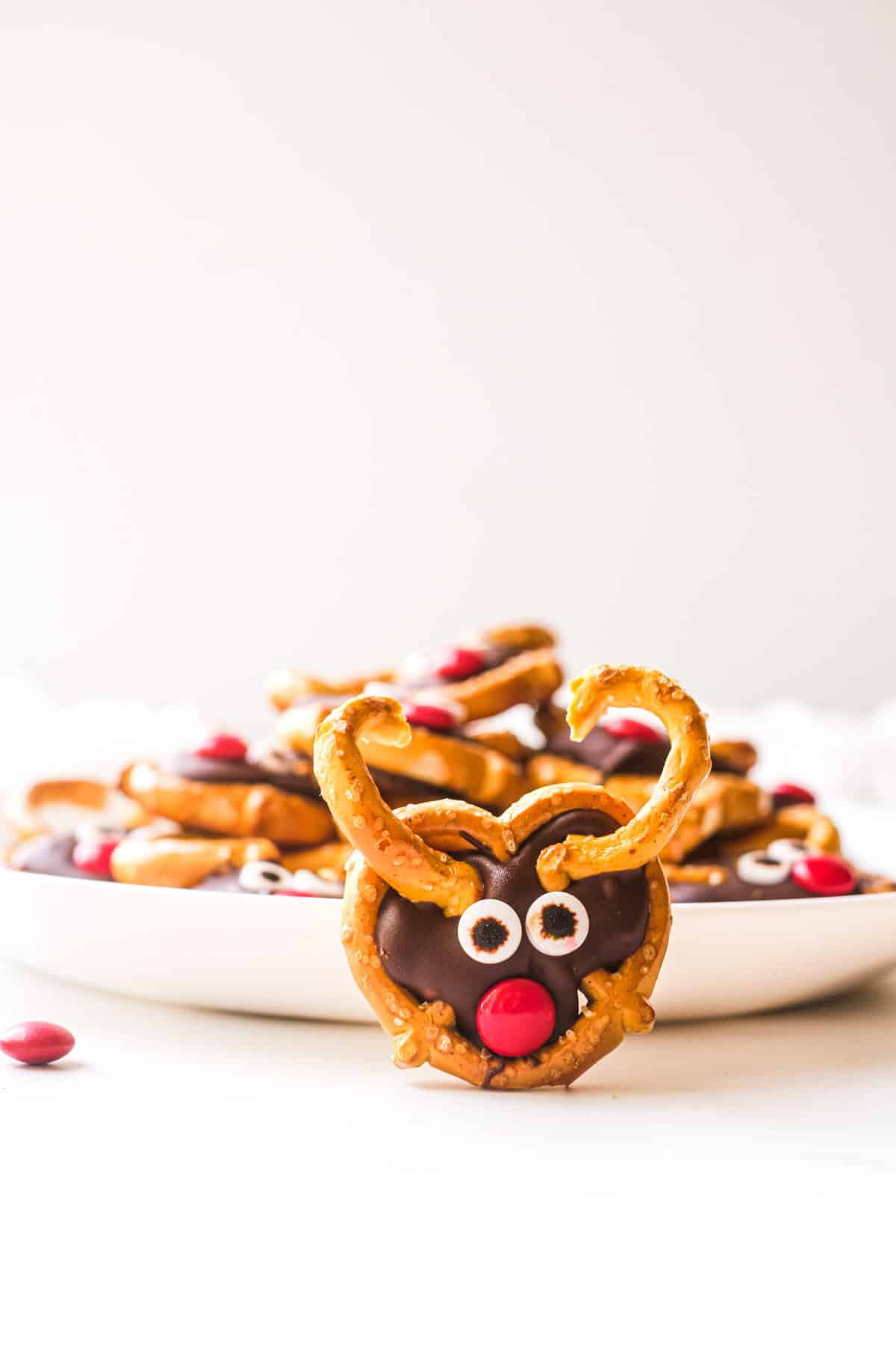a colorful pretzel reindeer on a table with a pile of them on a plate behind