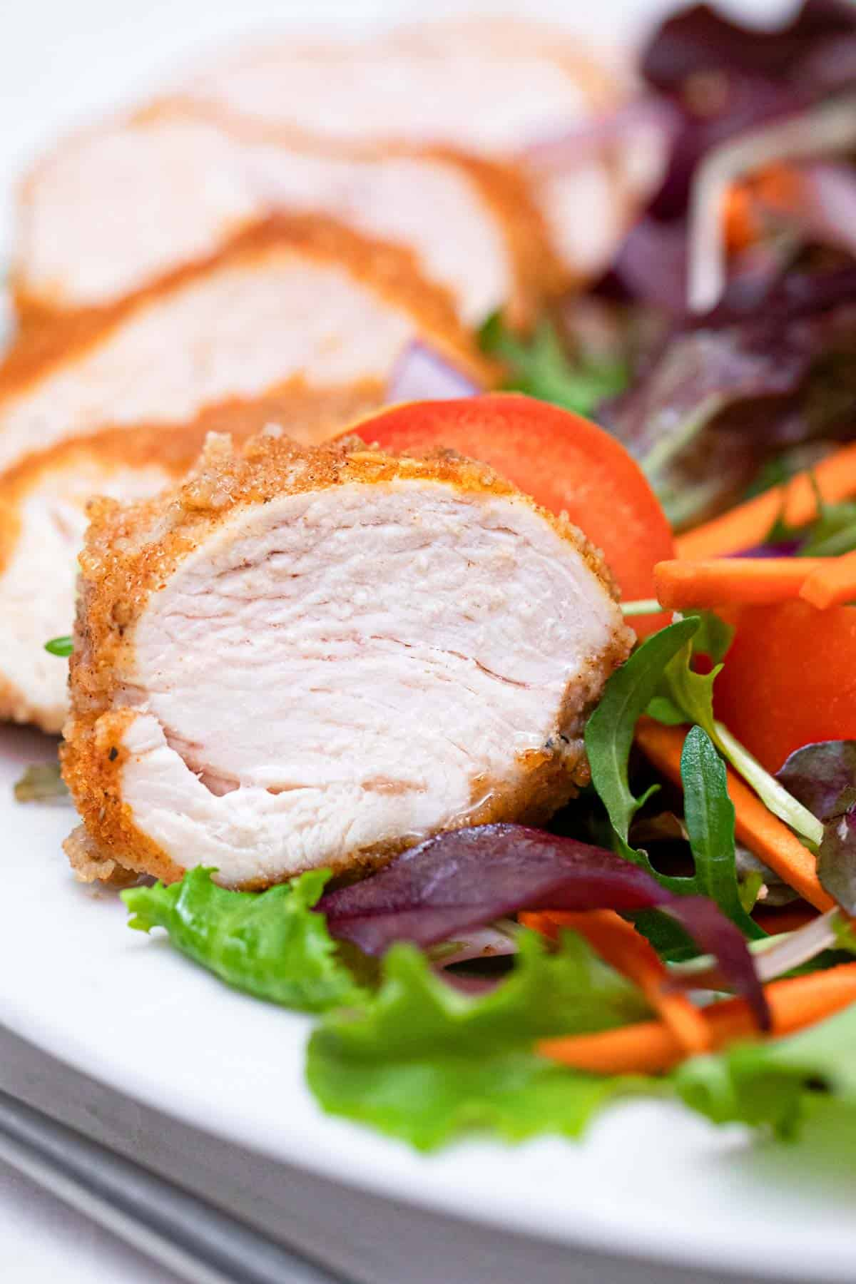 the finished air fryer chicken breast sliced and served on a plate with a green salad