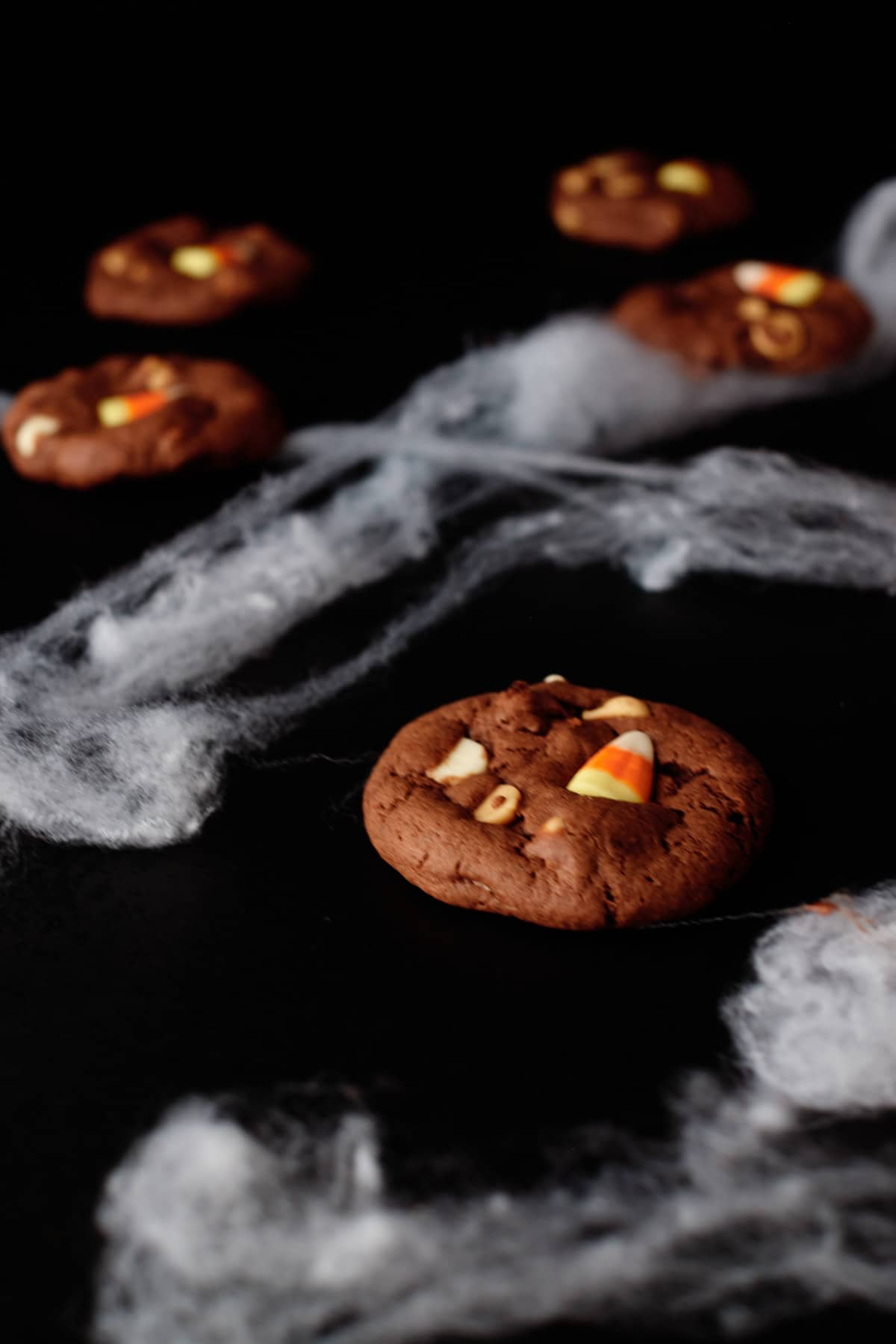candy corn cookies served on a black mat with fake spider web decor