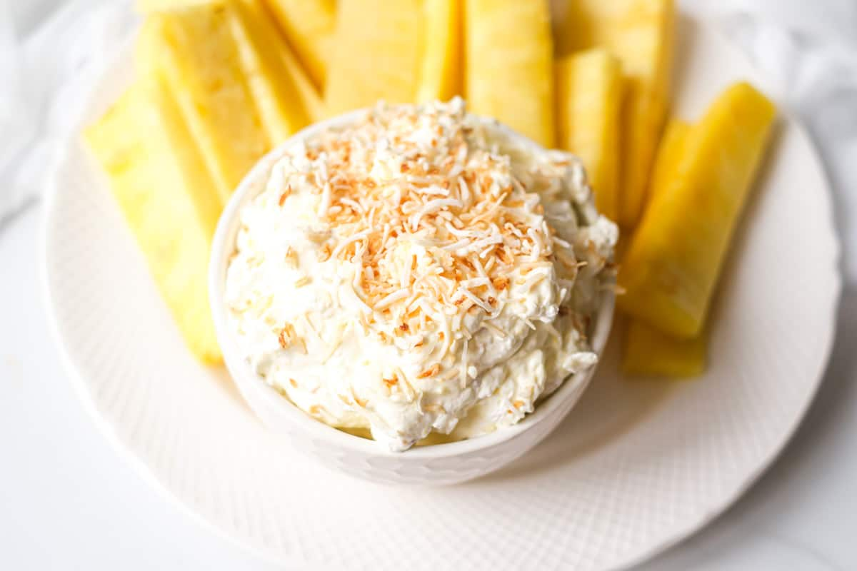 the finished cream cheese fruit dip served on a white bowl with fresh pineapple slices