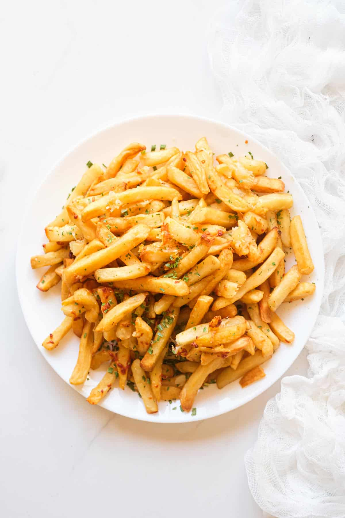 a white plate filled with garlic parmesan fries