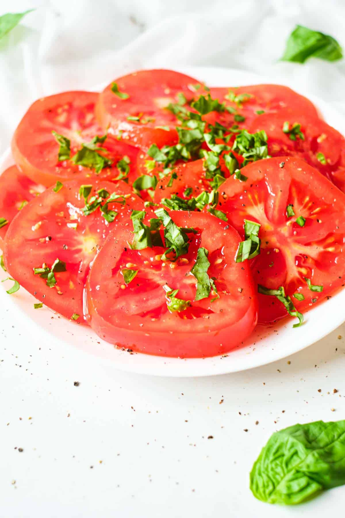 a white plate filled with marinated tomatoes