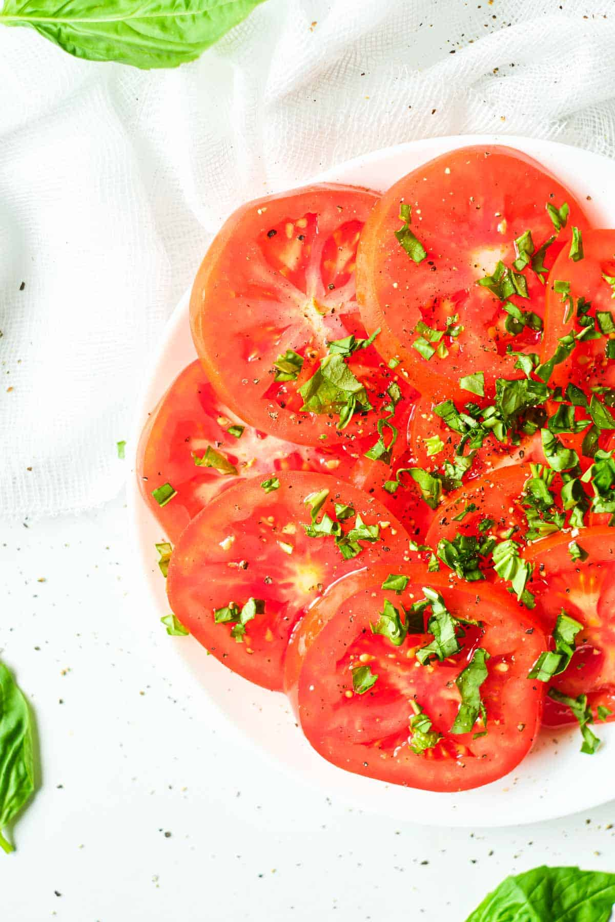 top down view of a plate filled with marinated tomatoes and basil