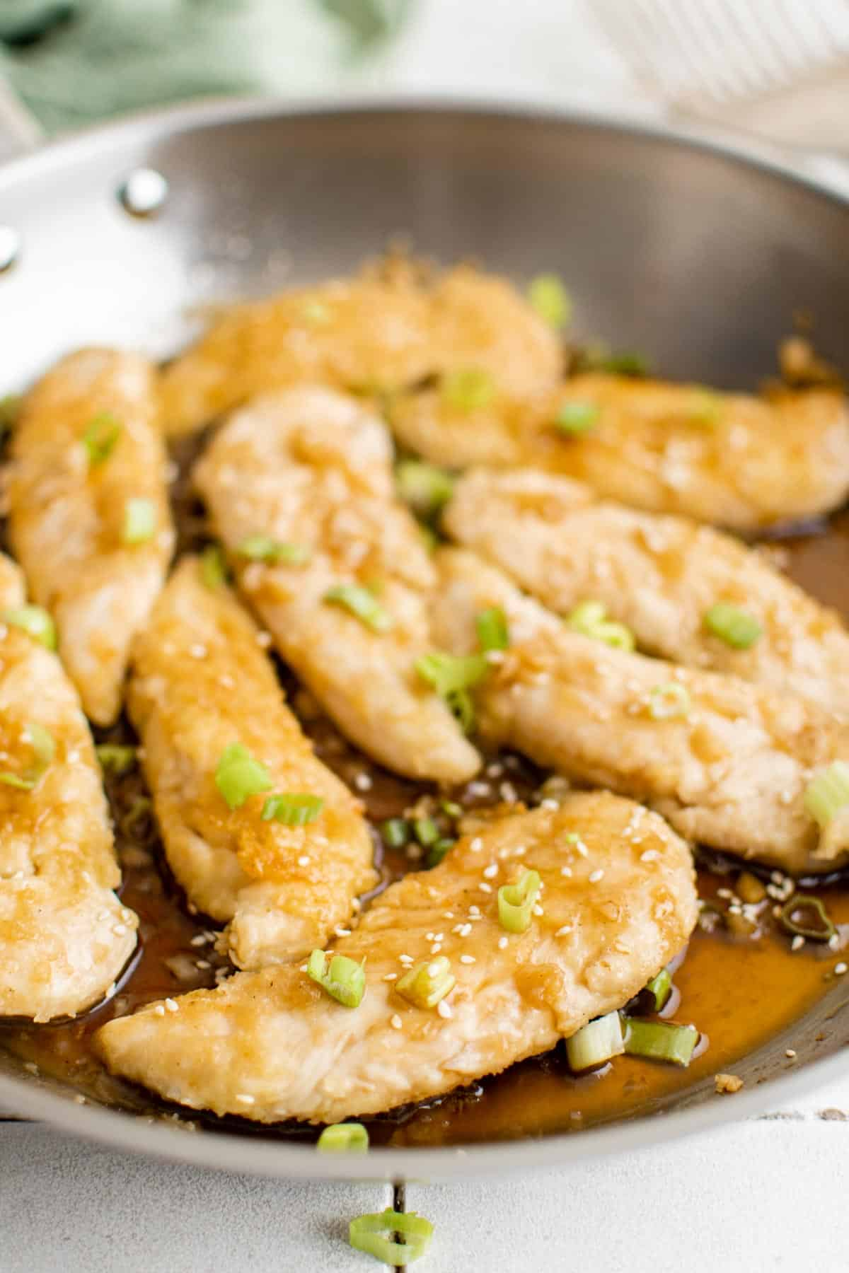 the completed chicken tender recipe with honey garlic sauce inside the pan