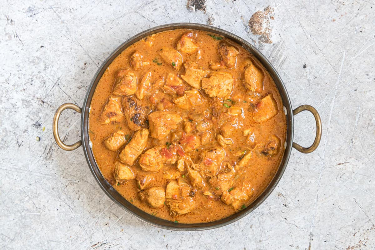 the completed instant pot chicken curry served in a stainless steel dish