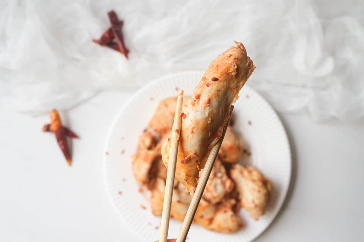 a pair of chopsticks holding one of the cooked instant pot chicken tenders
