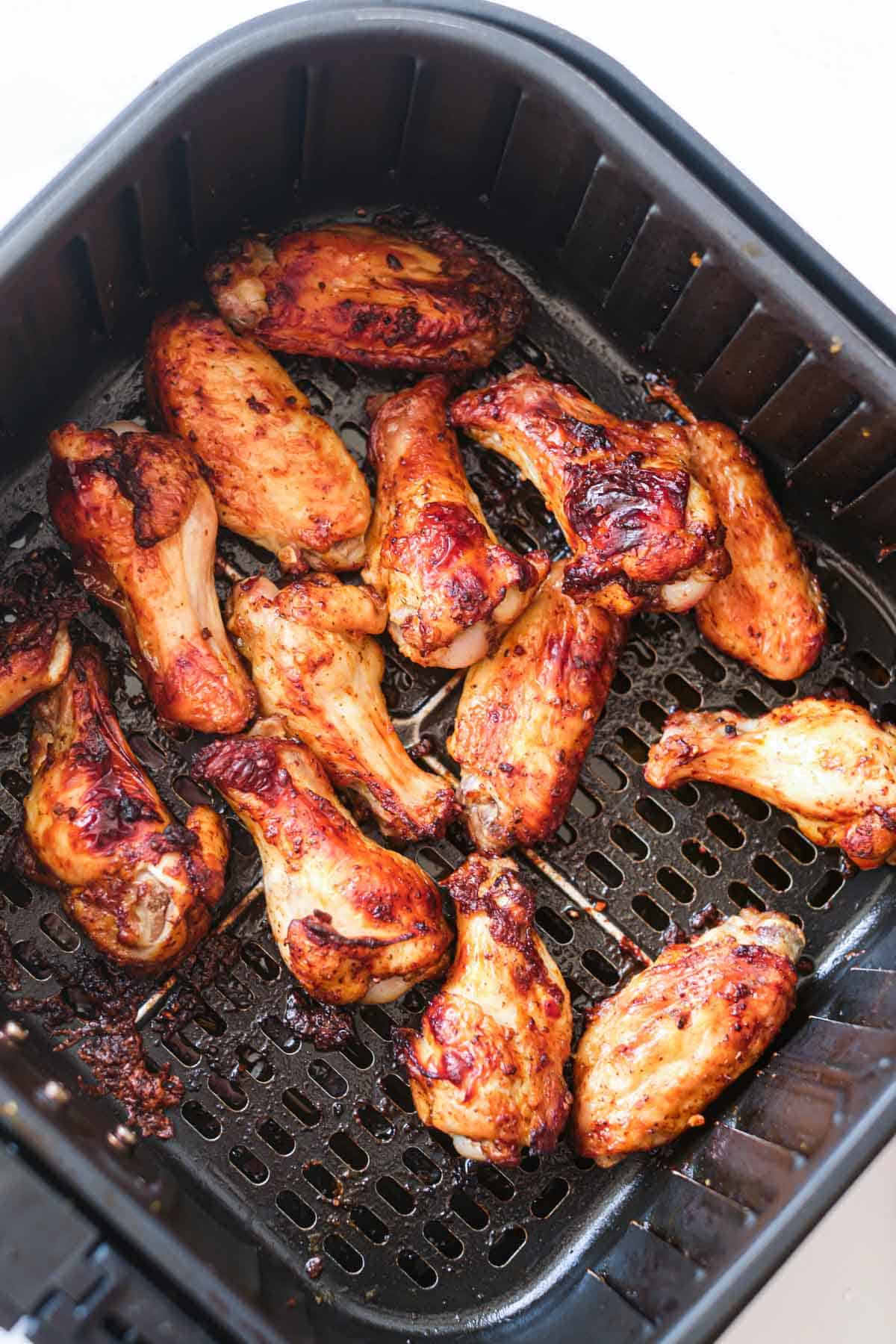 the cooked jerk chicken wings inside the air fryer basket