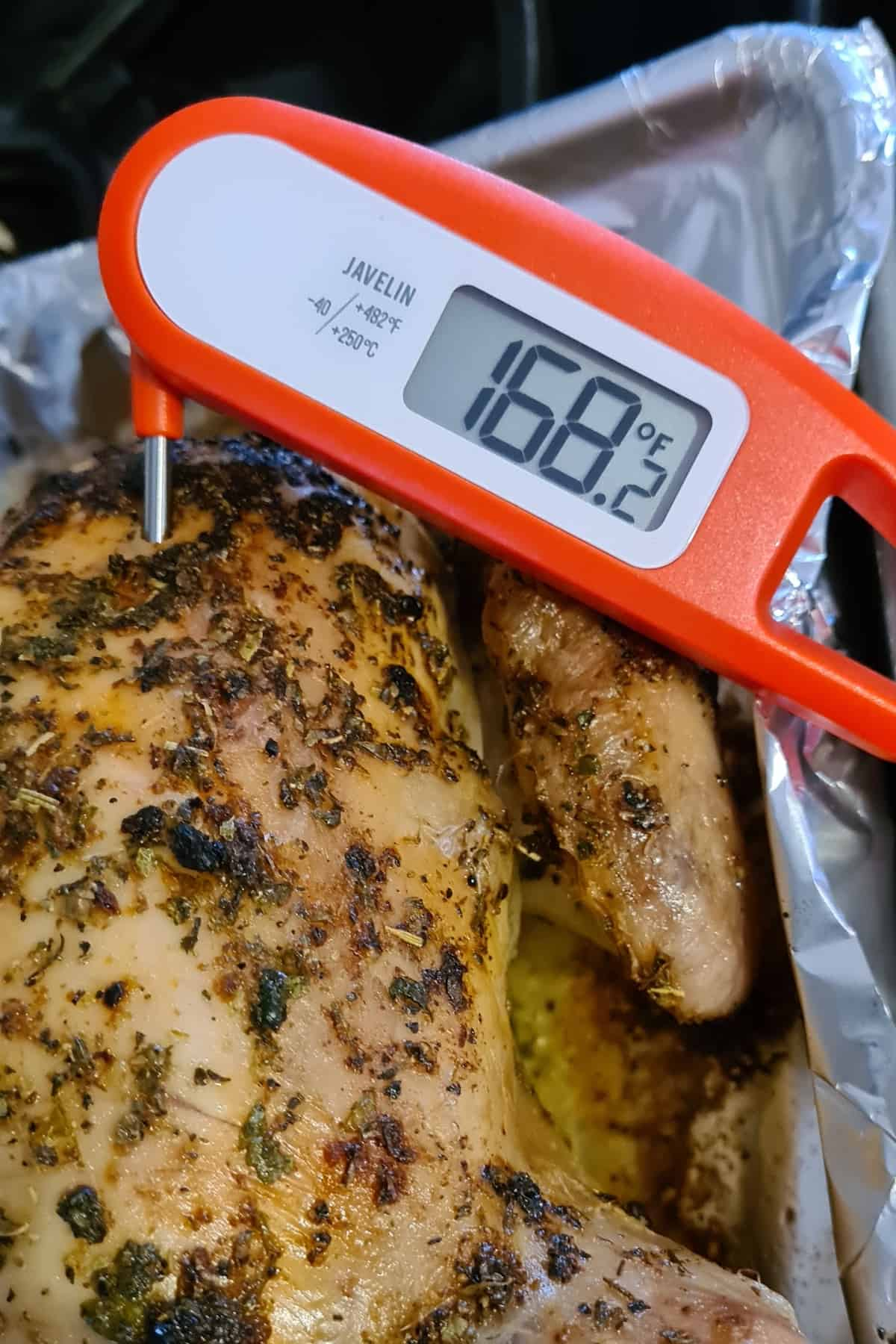 Close up view of the a meat thermometer inserted into a roast chicken that has reached the correct internal temperature