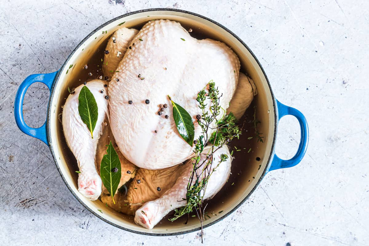a chicken in brine inside a large stock pot