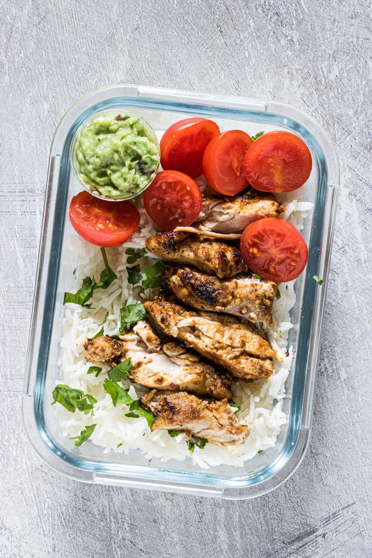 one portion of meal prep chicken and rice in a glass storage container