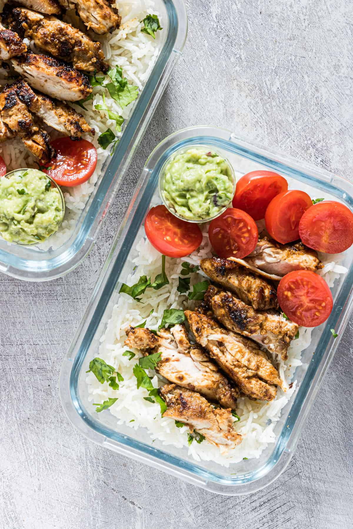 two servings of meal prep chicken and rice in glass containers