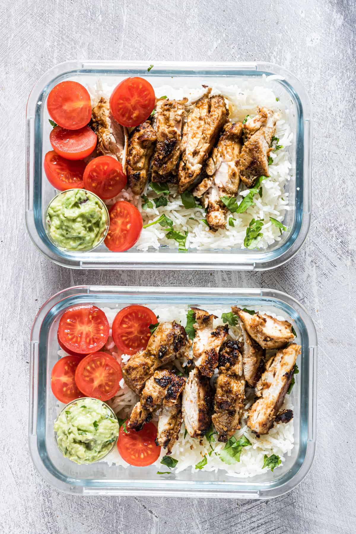 top down view of two completed meal prep chicken and rice servings