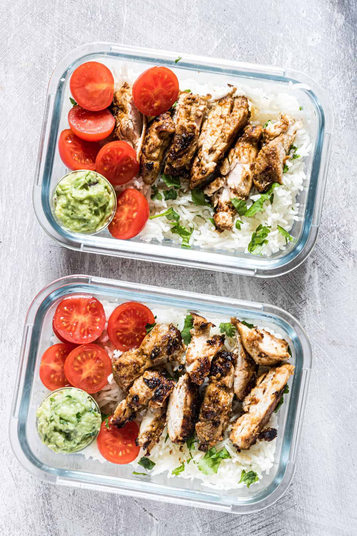 two portions of the finished meal prep chicken and rice