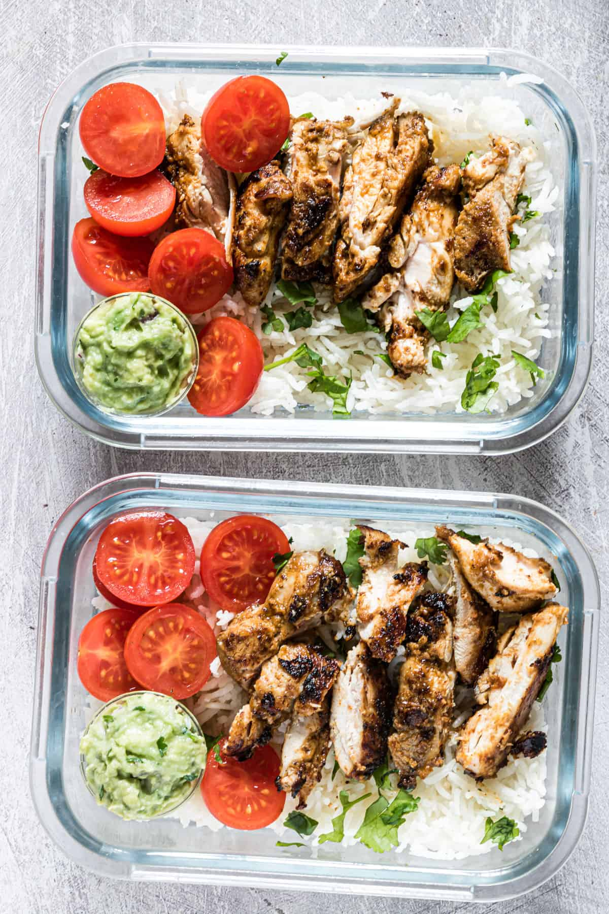 top down view of two meal prep chicken and rice servings inside glass storage containers