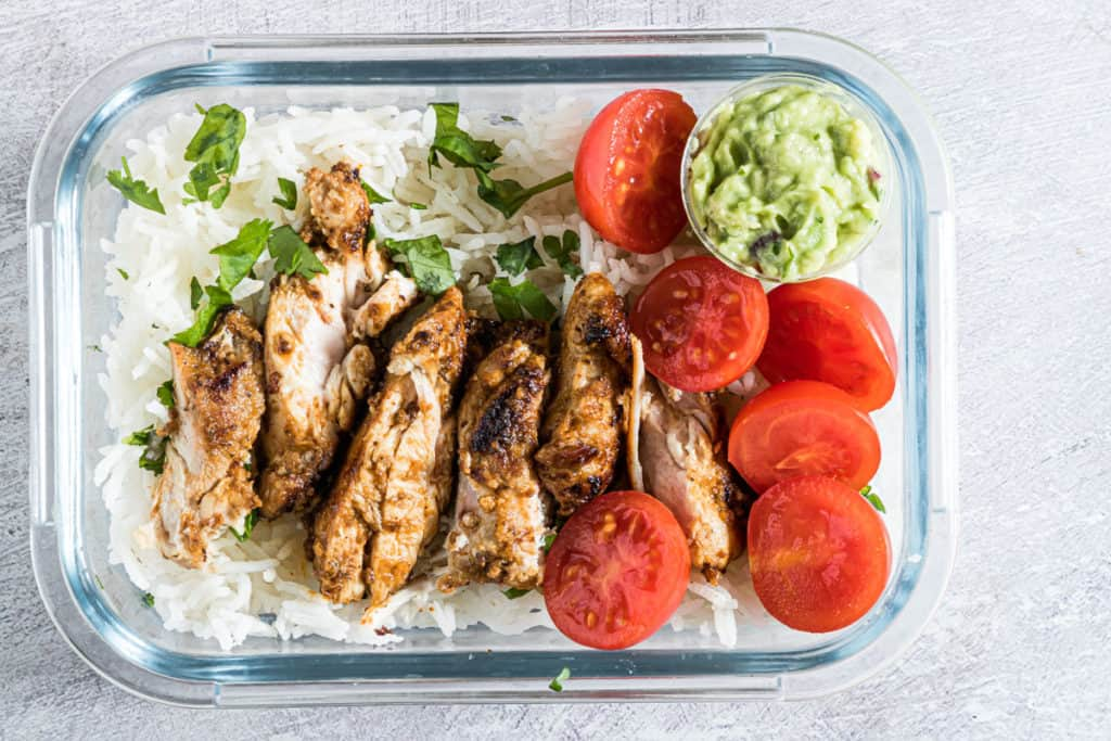 close up view of a glass meal prep container filled with the meal prep chicken and rice recipe