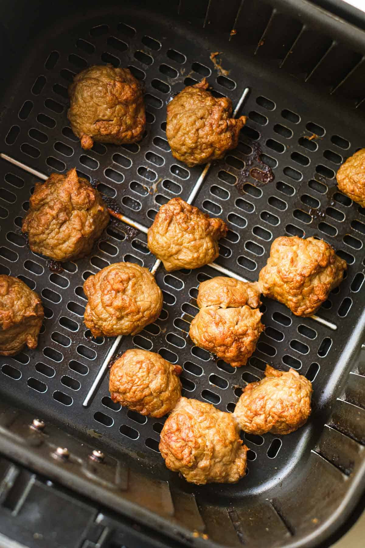 close up view of the cooked buffalo chicken meatballs inside the air fryer basket