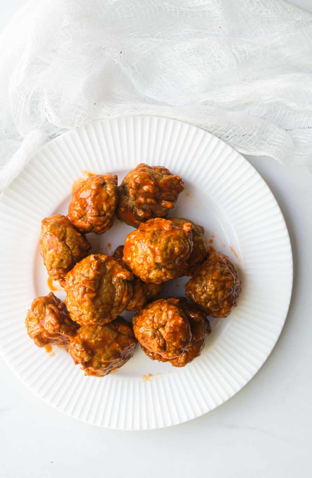 a white plate filled with the finished buffalo chicken meatballs