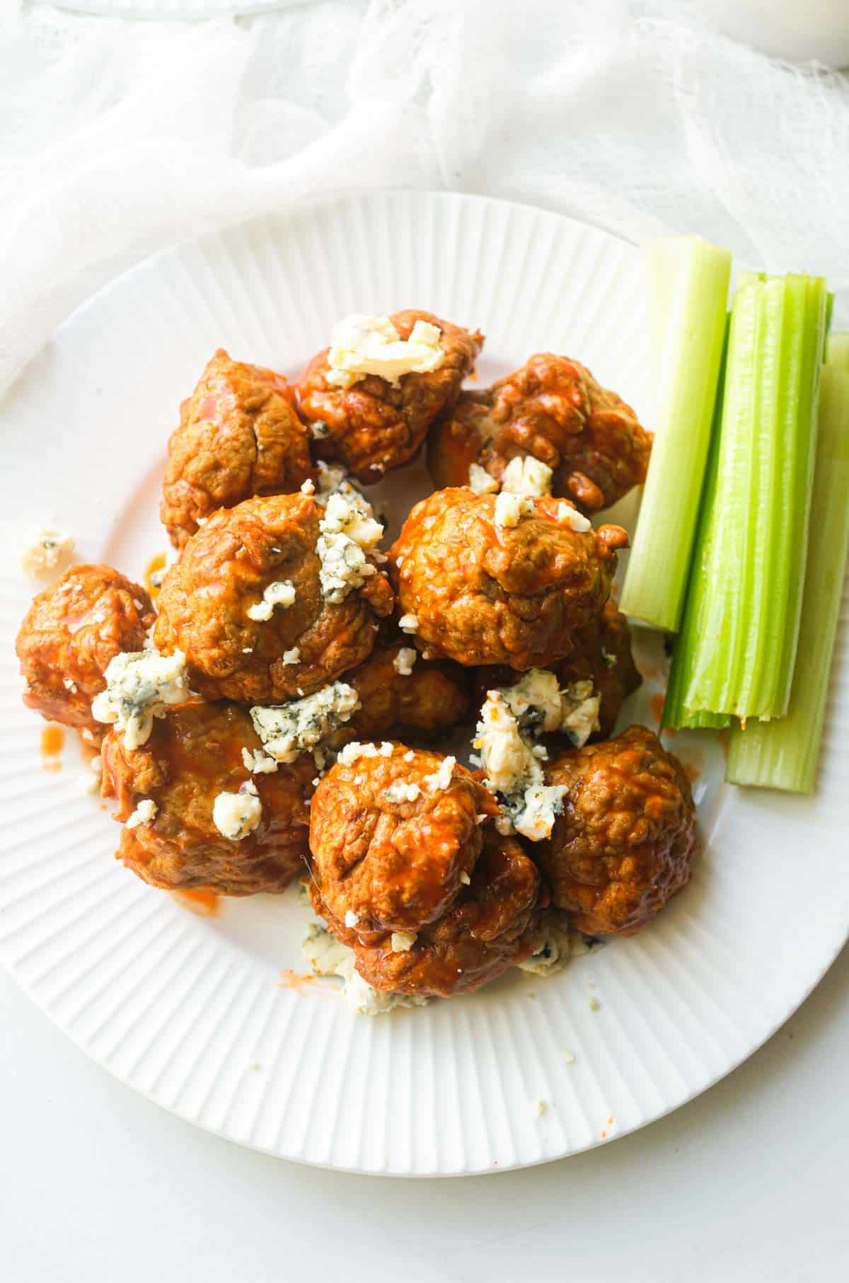top down view of the finished buffalo chicken meatballs on a white plate