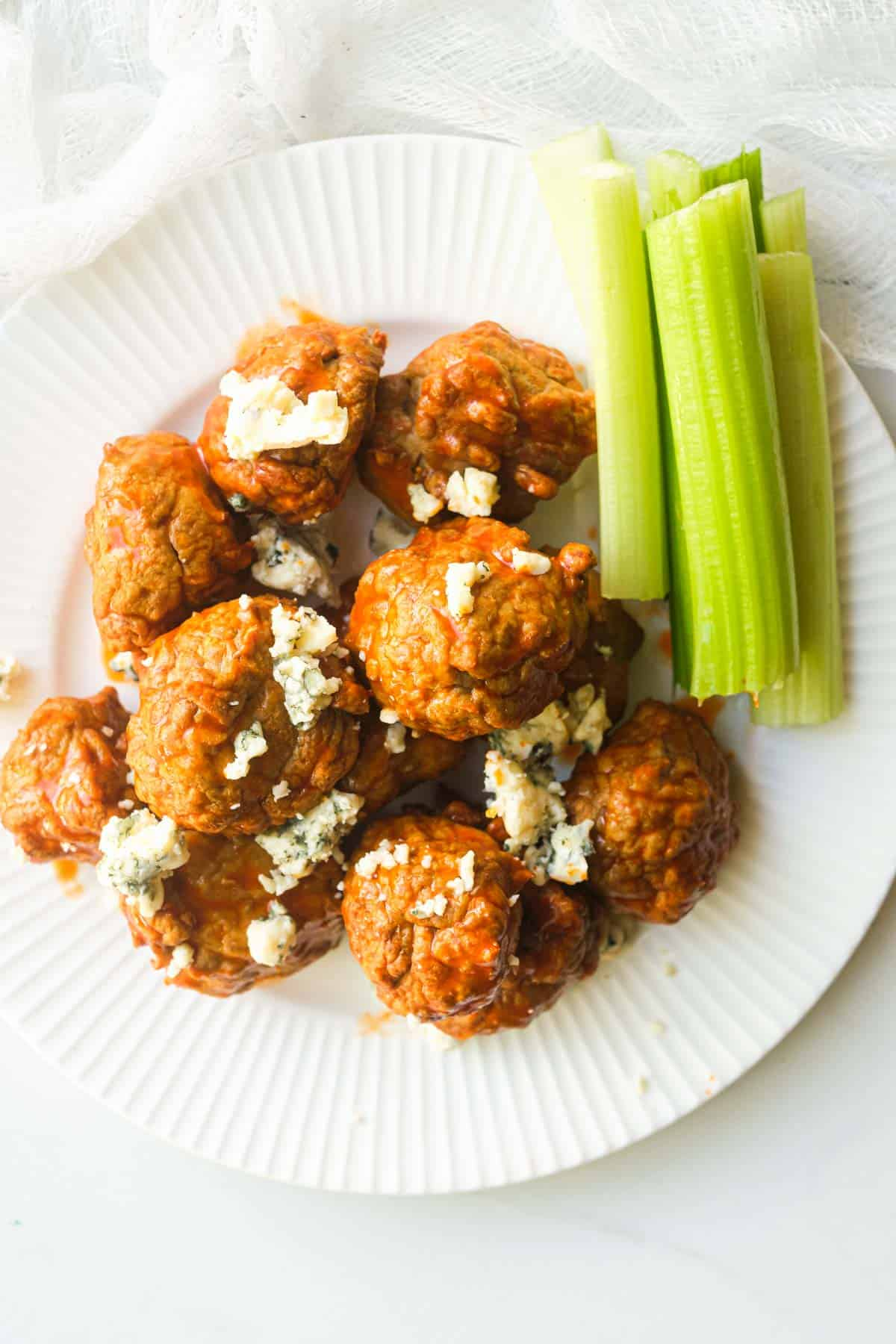 one serving of buffalo chicken meatballs with celery and blue cheese