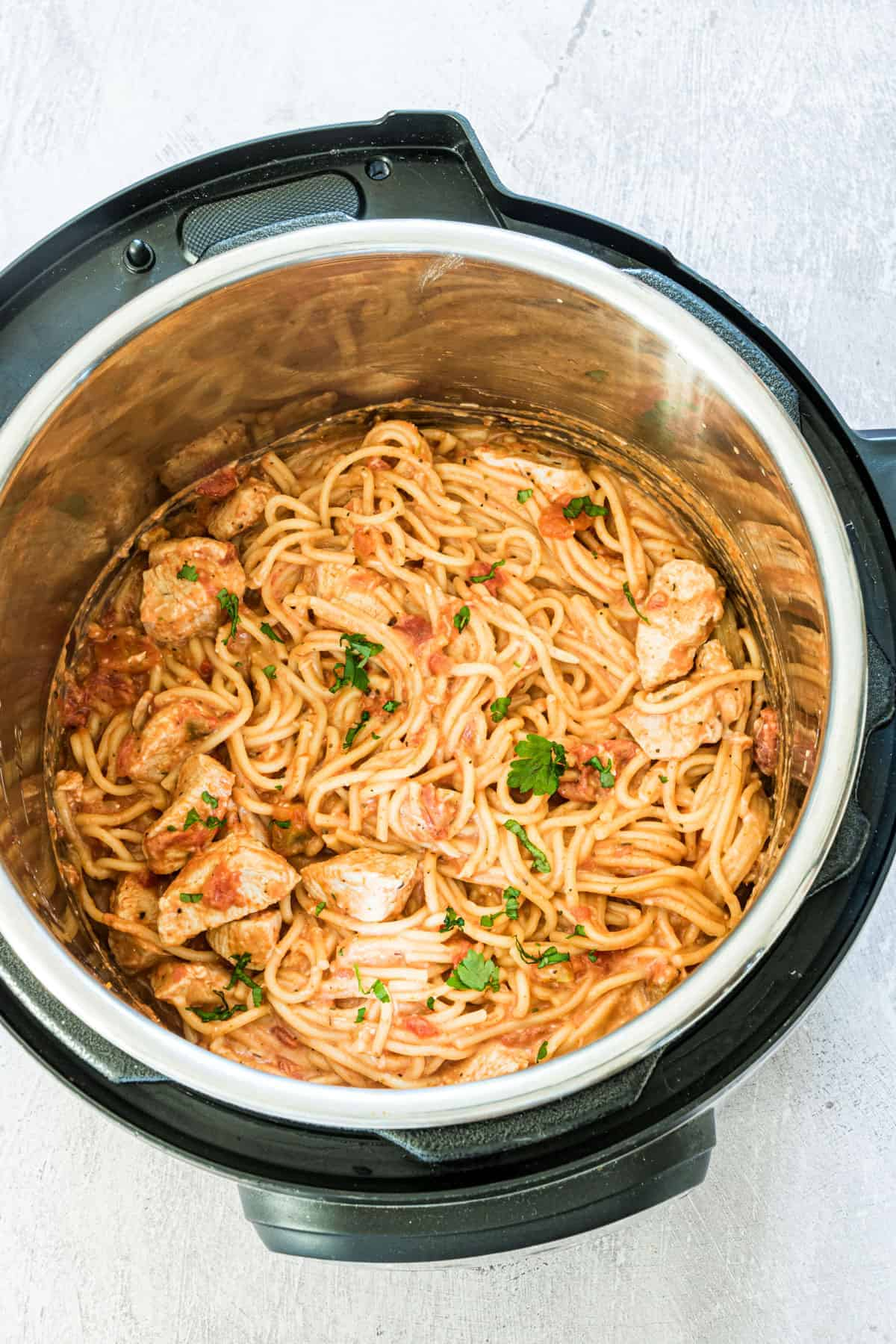 Instant Pot Chicken Spaghetti in an instant pot with herb garnish